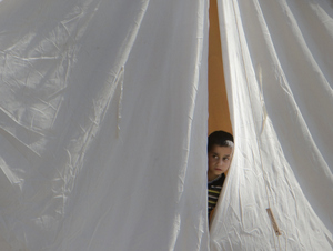 In this June 14, 2011 file photo, a Syrian refugee boy peers from a tent, in a camp, in Boynuyogun, Turkey. What appeared an unstoppable groundswell for change across the Middle East earlier this year, has splintered into scattered and indecisive conflicts that have left thousands dead and Western policy makers juggling roles ranging from NATO airstrikes in Libya to worried bystanders in Syria and Yemen.(AP Photo/Vadim Ghirda,File)